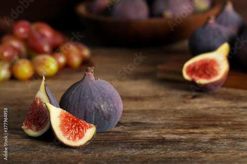 Fototapeta Whole and cut tasty fresh figs on wooden table. Space for text obraz