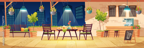 фотография Summer terrace, night outdoor city cafe, coffeehouse with wooden table, chairs, illumination and potted plants, chalkboard menu on cityscape view