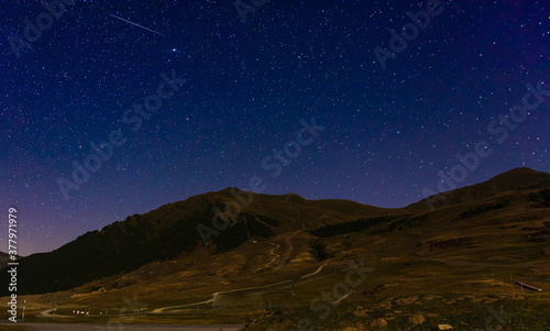Fototapeta Panoramic shot of a mountain landscape on a stary night background obraz