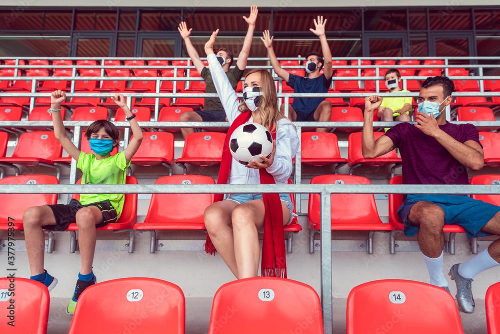 Fototapeta Fans watching football match under social distancing measures