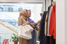 Side View Portrait Of Two Middle-Eastern Young Women Choosing Clothes While Enjoying Shopping In Mall, Copy Space