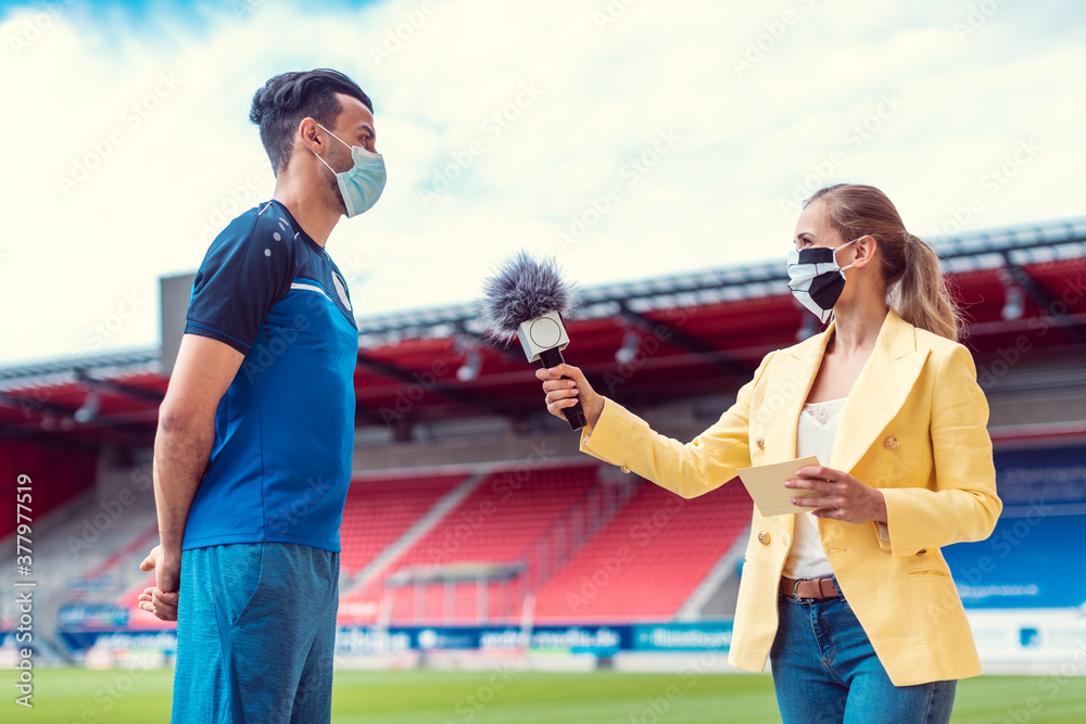 Fototapeta Reporter doing interview with football player during covid-19