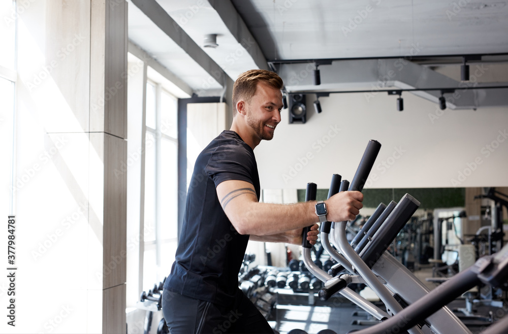 Fototapeta side view portrait of caucasian man workout on a fitness machine at gym, run, healthy lifestyle, sport concept