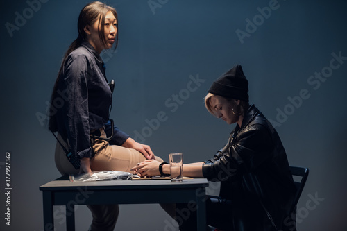 Fotografie, Obraz A young female asian police officer interrogates a girl's witness at the police station