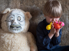 Funny Blond Boy In Blue Shirt And Jeans Inflates Several Colorful Balls At Same Time And Holds Them In His Mouth. Boy's Favorite Toy Teddy Bear Dressed In Zombie Mask