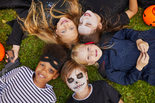 Above view at multi-ethnic group of kids wearing Halloween costumes while lying Tapéta, Fotótapéta
