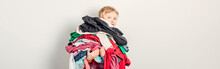 Mommy Little Helper. Adorable Funny Child Arranging Organazing Clothing. Kid Holding Messy Stack Pile Of Clothes Things. Home Chores Housework For Kids. Web Banner Header.