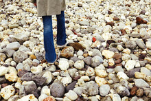 Child Walking On The Pebbles A...