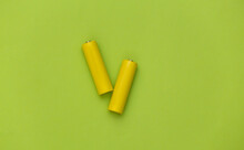 Two Yellow AA Battery On Green...