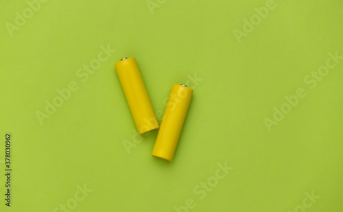 Fotografía Two yellow AA battery on green pastel background. Top view