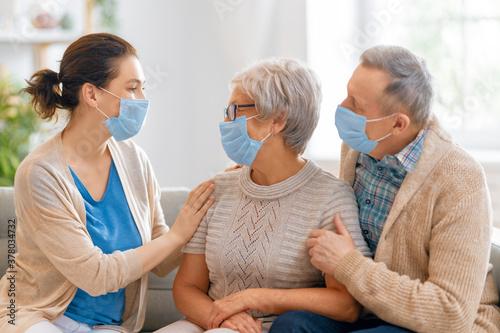 Fototapeta Adult daughter and senior parents wearing facemasks