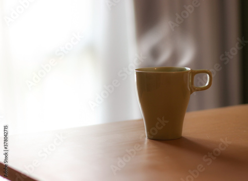 Fototapeta Coffee mugs or hot beverages can be placed on a table by the window and can be used as a background or wallpaper