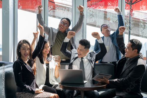 Selective focus of a Businessman raising arms to celebrate business success with his colleague in the coffee lounge. Group of cheerful employee, company staff, and workers working in public places.
