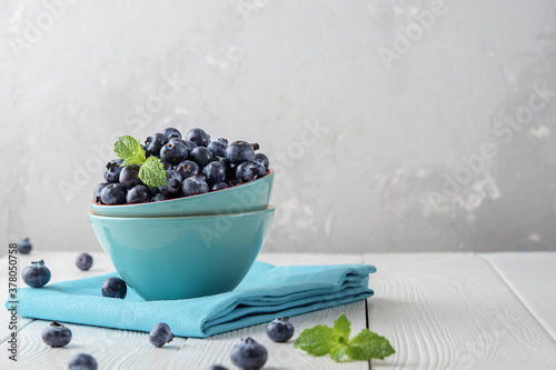 Fotografia Fresh blueberries in a blue bowl on a light wooden table with copies of space