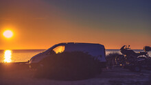 Camper Van With Motorcycle At Sunset
