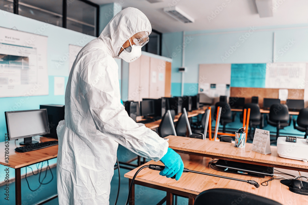 Fototapeta Worker in white sterile uniform, with rubber gloves and mask on holding sprayer with disinfectant and sterilizing informatics cabinet in school.