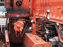 Old Hydraulic Cylinder And Control Lever. It Is Installed Behind The Red Truck Cabin For Steering The Cable Car. Focus Close And Choose The Subject.