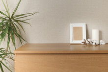 Wooden Chest Of Drawers With A White Candle, A White Photo Frame With A Cotton Branch On A Light Wall, On The Left Is A Living Plant Dracaena