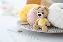 Crocheted Bear And Knitting Supplies On White Wooden Table. Engaging In Hobby