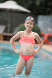 smiling child wearing swimming glasses in swimming pool. little girl playing in outdoor swimming pool on summer vacation on tropical beach island. child learning to swim in pool of luxury resort.