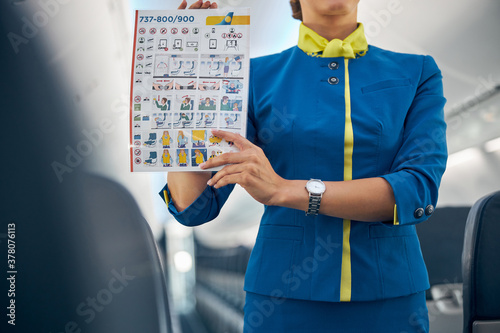 Fotografia, Obraz Young attractive air hostess holding safety instructions on a commercial flight