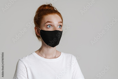 Fototapeta Image of shocked ginger girl in face mask posing and looking aside obraz