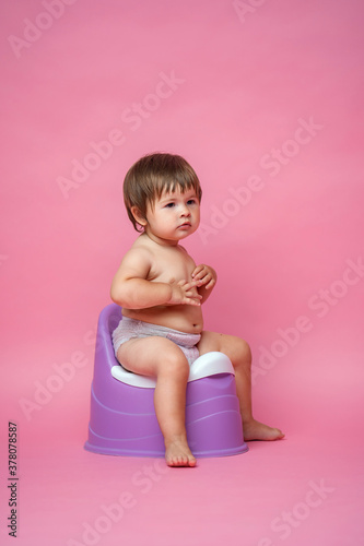 Cute baby in a diaper sitting on a potty Wallpaper Mural