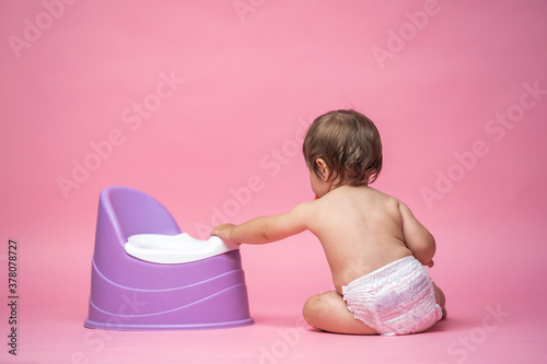 cute baby in a diaper is sitting next to a pot Wallpaper Mural