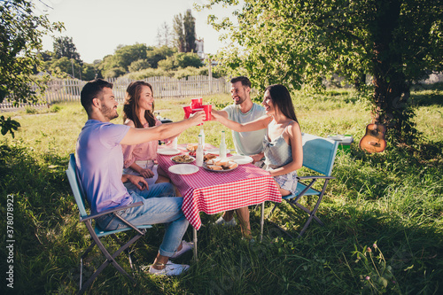 Fototapeta Portrait of four people nice attractive cheerful best buddy fellow guys group fresh air spending weekend sunny day drinking beverage clinking cups meeting vacation holiday backyard house obraz