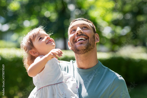 Obraz family, fatherhood and people concept - happy smiling father with baby daughter at summer park - fototapety do salonu