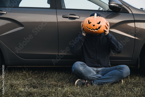 Obraz na plátně An unrecognizable adult man sits near a car on the grass and holds in front of his face a carved pumpkin for Halloween, outdoors