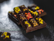 Handmade Pieces Of Dark Chocolate With Pieces Of Dried Fruit, On A Black Leather Surface, Backlighting