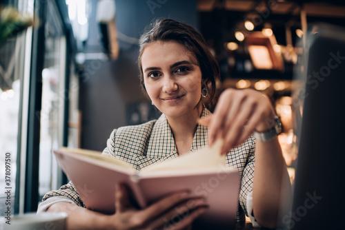 Fotografie, Tablou Half length portrait of Caucasian female student holding education textbook whil