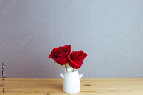 Valokuvatapetti Red rose flowers in vase on wooden table with gray background