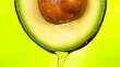 Leinwandbild Motiv Fresh cut avocado with oil stream. Concept of healthy fruit also useful in cosmetics.