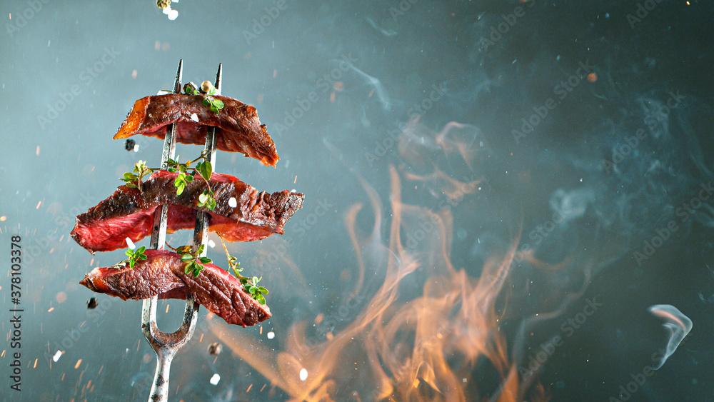 Leinwandbild Motiv - Lukas Gojda : Close-up of tasty beef steak on black fork, fire flames in foreground