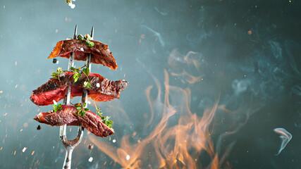 Fototapeta Boks Close-up of tasty beef steak on black fork, fire flames in foreground