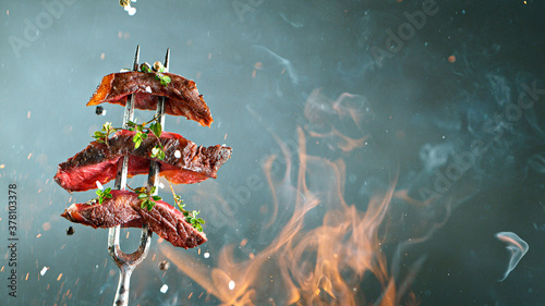 Close-up of tasty beef steak on black fork, fire flames in foreground