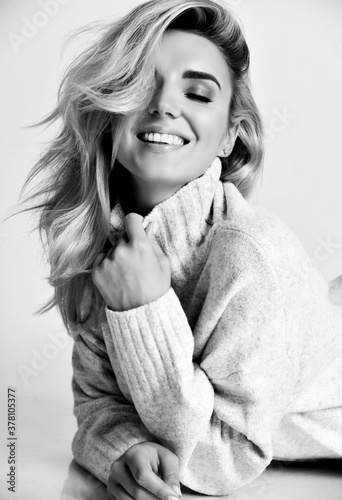 Portrait of young sexy smiling blonde woman model in cosy warm sweater