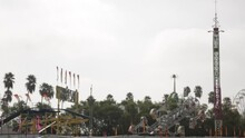 Rides At The Fair Ready Before Opening, Palm Trees And A Cloudy Gloomy Sky
