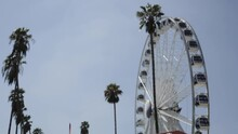 Empty Ferris Wheel At Fair Spins In Slow Motion, Blue Sky And Palm Trees, Low Angle