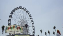 Empty Ferris Wheel Spins, Candy Concessions Counter And Palm Trees, Slow Motion Low Angle