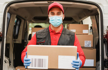 Portrait Of Delivery Man Wearing Face Protective Mask For Coronavirus Spread Prevention - Courier At Work During Covid 19 Pandemic Time