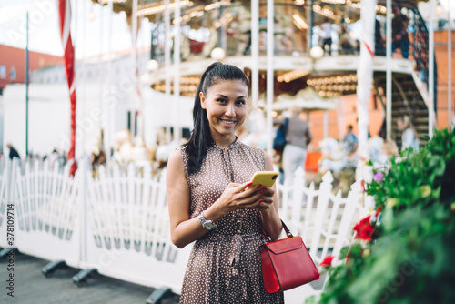 Fényképezés Half length portrait of sincerely hipster girl with mobile technology in hands s