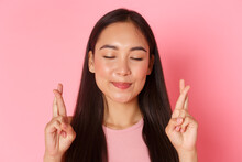 Beauty, Fashion And Lifestyle Concept. Close-up Of Hopeful Optimistic Asian Girl Making Wish, Close Eyes And Smiling Relaxed While Cross Fingers Good Luck And Praying Dream Come True, Pink Background