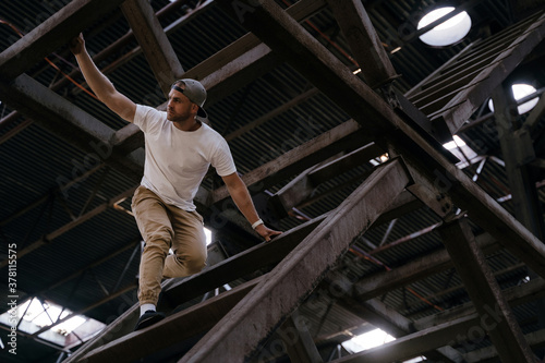 Fototapeta Young athletic man is climbing high on metallic bridge construction, tracer practicing parkour outdoor