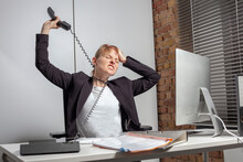 Totally Depressed Young Female Employee At Work With Tangled Telephone Cable Around Her Neck