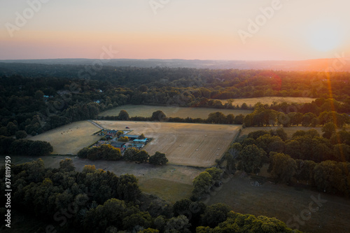 Fototapeta Aerial shot of farmland and house surrounded by woodland in Surrey, UK. Sunset obraz