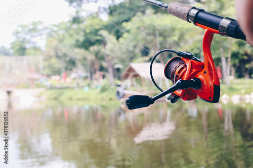 Close up of spinning with the fishing reel in the hand, fishing hook on the line with the bait in the left hand against the background of the water Tableau sur Toile