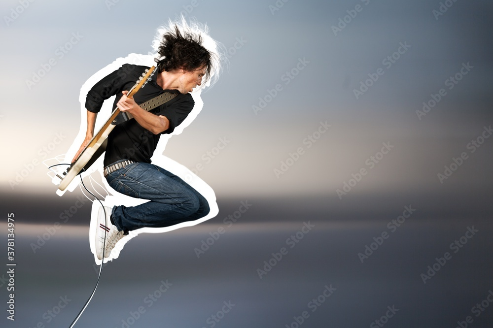 Fototapeta Male guitarist playing music on guitar and jump